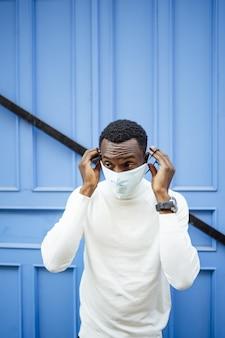 Pionowe ujęcie czarnego mężczyzny w masce sanitarnej