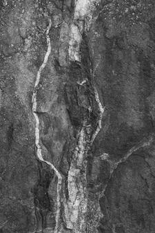 Pionowe ujęcie czarnej, szorstkiej ściany betonowej