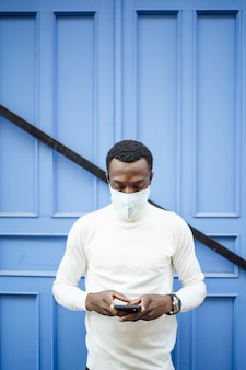Pionowe ujęcie czarnoskórego mężczyzny patrzącego na swój telefon w masce sanitarnej