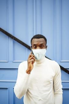 Pionowe ujęcie czarnoskórego mężczyzny rozmawiającego przez telefon w masce sanitarnej