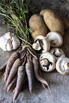 Pionowe ujęcie czosnku, ziemniaków, grzybów i marchwi na powierzchni drewnianych