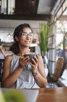 Pionowe ujęcie delikatna delikatna zrelaksowana kobieta miejska w okularach, ciesząc się chwilą siedzącą samotnie w kawiarni