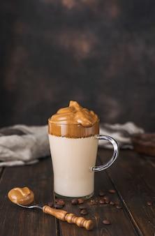 Pionowe ujęcie delikatnej pienistej i kremowej modnej bitej kawy dalgona