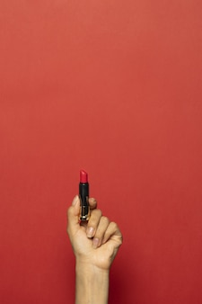 Pionowe ujęcie dłoni trzymającej szminkę na czerwonej ścianie