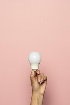 Pionowe ujęcie dłoni trzymającej żarówkę na białym tle na różowej powierzchni
