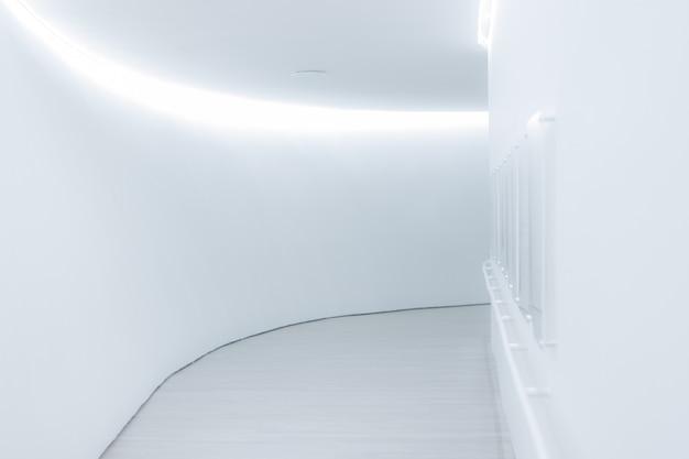 Pionowe ujęcie doskonale oświetlonego, białego korytarza