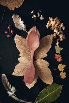Pionowe ujęcie drewnianą łyżką otoczone liśćmi i piórami różnych roślin