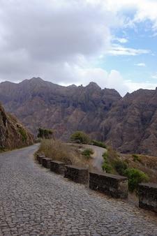 Pionowe ujęcie drogi w środku formacji skalnych pod zachmurzonym niebem