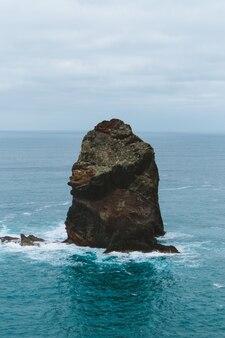 Pionowe ujęcie dużego kamienia na środku oceanu zrobionego na maderze w portugalii