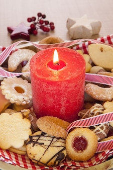 Pionowe ujęcie dużej czerwonej świecy z christmas cookies i ozdoby