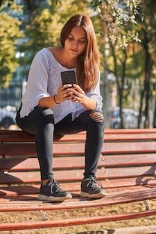 Pionowe ujęcie dziewczyny siedzącej na ławce i patrząc na swój telefon