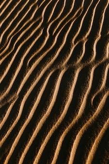 Pionowe ujęcie falistego piasku ze świecącym na nim słońcem