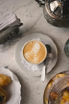 Pionowe ujęcie filiżanki cappuccino na marmurowym stole z deserami