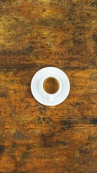 Pionowe ujęcie filiżanki kawy na drewnianym stole