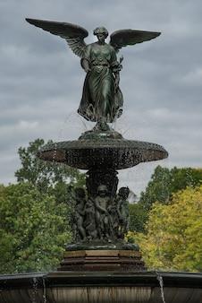 Pionowe ujęcie fontanny bethesda w nowym jorku, usa z ponurym niebem w tle