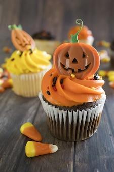 Pionowe ujęcie halloweenowych babeczek z kolorowymi upiornymi dodatkami na stole