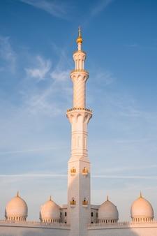 Pionowe ujęcie historycznego wielkiego meczetu szejka zayeda w abu dhabi, zjednoczone emiraty arabskie na tle błękitnego nieba