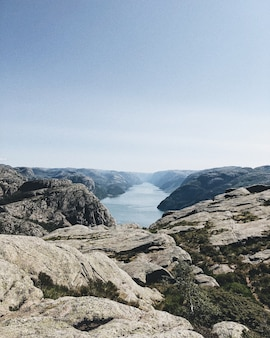 Pionowe ujęcie jeziora otoczonego przez formacje skalne pod bezchmurnym niebem