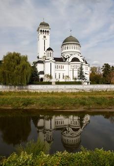 Pionowe ujęcie katedry świętej trójcy, odzwierciedlając w jeziorze w sighisoara w rumunii