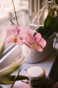 Pionowe ujęcie kawy umieszczonej obok kwiatka na parapecie