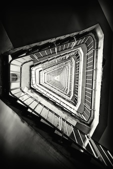 Pionowe ujęcie klatki schodowej w budynku w skali szarości