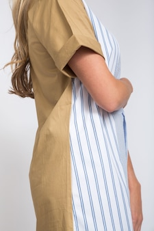 Pionowe ujęcie kobiety noszącej sukienkę z przodu w paski iz tyłu w kolorze beżowym