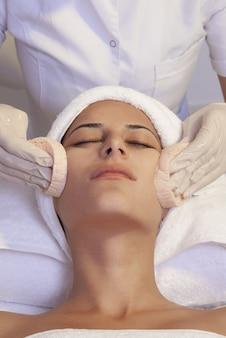 Pionowe ujęcie kobiety o idealnej skórze, ręcznik na głowie z profesjonalistą pielęgnacji skóry