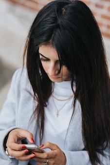 Pionowe ujęcie kobiety rasy kaukaskiej patrząc na swojego smartfona