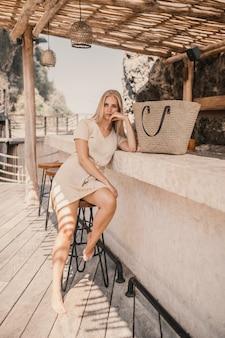 Pionowe ujęcie kobiety siedzącej obok stoiska barowego w ciągu dnia