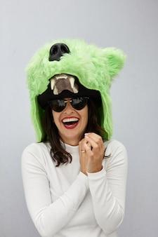 Pionowe ujęcie kobiety śmiejącej się z kapeluszem niedźwiedzia
