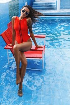 Pionowe ujęcie kobiety w czerwonym stroju kąpielowym i okularach przeciwsłonecznych, siedząc krzesełko ratownika na basenie.