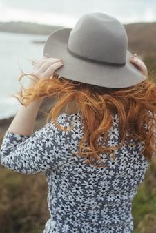 Pionowe ujęcie kobiety w kapeluszu z morzem i drzewami na odległość