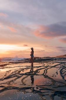 Pionowe ujęcie kobiety w szortach i kapeluszu stojącej na plaży podczas pięknego zachodu słońca