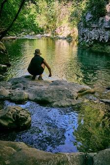 Pionowe ujęcie kogoś w pobliżu jeziora w parku przyrody arche de ponadieu