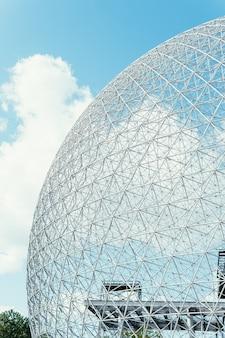 Pionowe ujęcie konstrukcji w kształcie kuli ziemskiej pod jasnym pochmurnym niebem