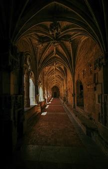 Pionowe ujęcie korytarza starego budynku z oknami i drzwiami w oddali