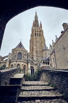 Pionowe ujęcie kościoła matki bożej w brugii w belgii na czystym niebie