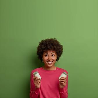 Pionowe ujęcie kręconej pozytywnej kobiety wygląda z uśmiechem powyżej, trzyma pyszny biały jogurt organiczny, nosi swobodny różowy sweter, pozuje przy zielonej ścianie, pusta przestrzeń w górę. zdrowe odżywianie