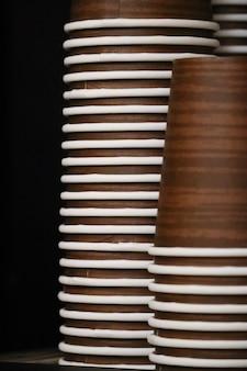 Pionowe ujęcie kubków papierowych ułożonych jeden na drugim