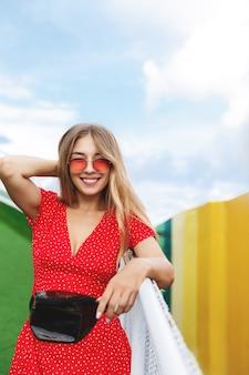 Pionowe ujęcie ładnej blond dziewczyny w letniej sukience i czerwonych okularach przeciwsłonecznych, opierając się na poręczy w parku.