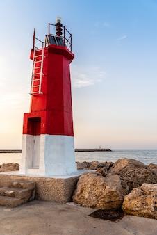 Pionowe ujęcie latarni morskiej w pobliżu morza pod błękitnym niebem