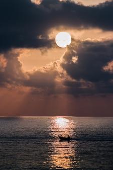 Pionowe ujęcie łodzi na morzu o zachodzie słońca
