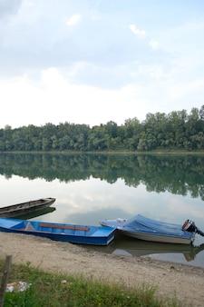 Pionowe ujęcie łodzi na rzece otoczonej zielenią pod zachmurzonym niebem
