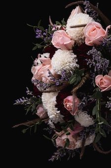 Pionowe ujęcie luksusowego bukietu różowych i czerwonych róż i białych dalii na czarnym tle