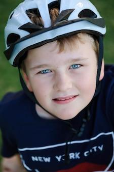 Pionowe ujęcie małego chłopca o niebieskich oczach i białym kasku