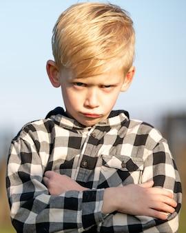 Pionowe ujęcie małego chłopca w flanelowej koszuli z uroczym grymasem na twarzy