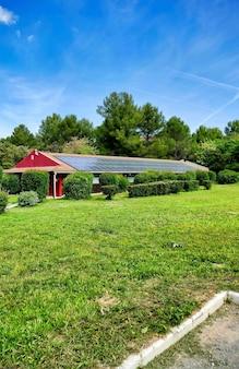 Pionowe ujęcie małego domu z panelami słonecznymi w zielonym polu na wyspach kanaryjskich