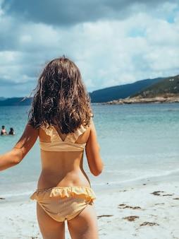 Pionowe ujęcie małej dziewczynki w bikini na plaży z tyłu