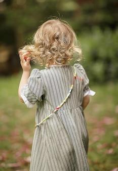 Pionowe ujęcie małej kaukaskiej dziewczyny w długiej sukni z plecami na zewnątrz