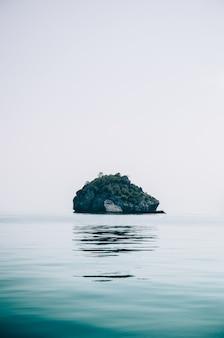 Pionowe ujęcie małej skalistej wyspy na środku oceanu, zrobione w tajlandii